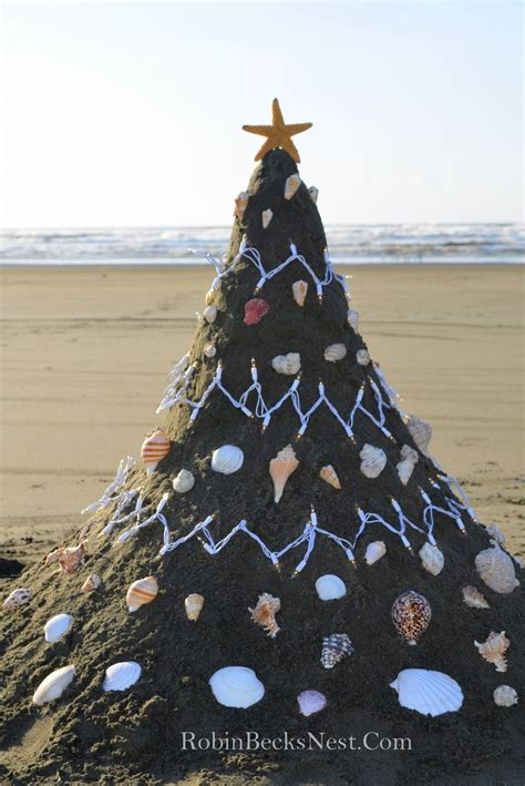 sand christmas tree on the beach decorated with lights and