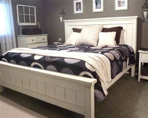 dark grey wooden bed with white leather headboard next to white leather king size platform bed frame with tufted
