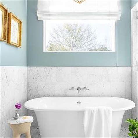 spa blue bathroom large crystal drum pendant light over oval bathtub