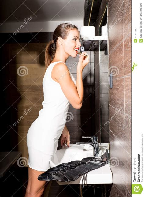 woman going to bathroom beautiful young woman putting on makeup in the bathroom