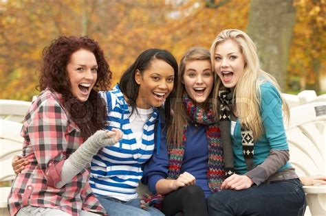 group teen girls laughing group of four teenage girls sitting on bench in autumn
