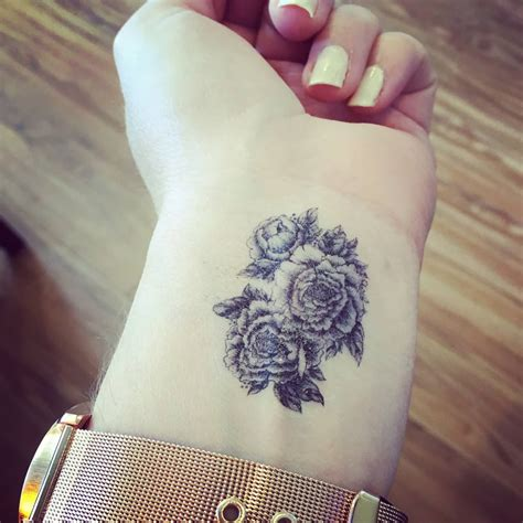 black ink peony flowers tattoo on left wrist