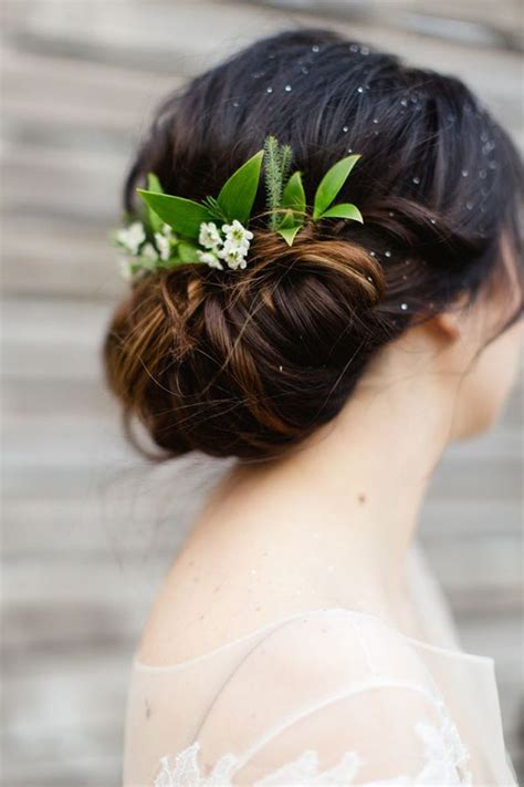 attach hair piece for contest low tied bun with greenery as hair piece brides with buns