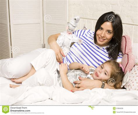 lay in bed portrait of mother and daughter laying in bed and smiling royalty free stock images