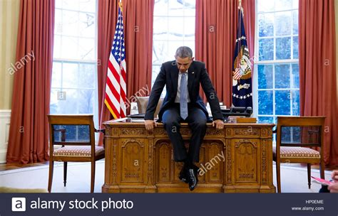 President Barack On His Desk In The Oval Office Before A White House Desk