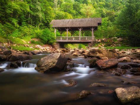 mountain stream wooden bridge rocks green forest north
