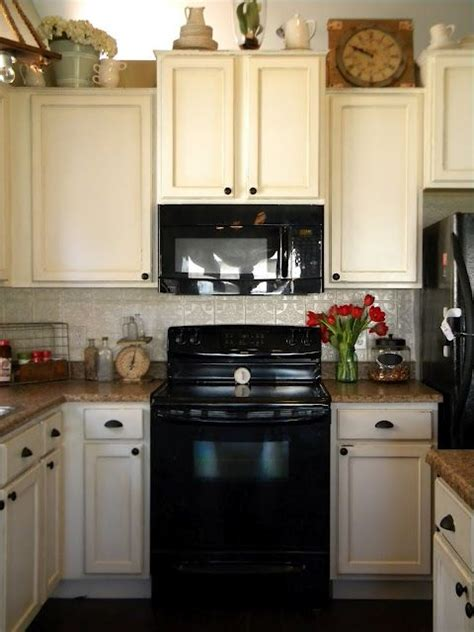 white cabinets  black appliances home kitchen