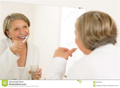 mature bathtub mature woman brushing teeth look bathroom mirror royalty free stock photography