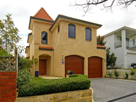 sandstone modern house exterior with brick fence hedging