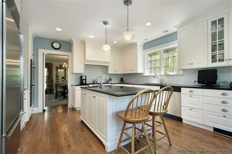 white cabinets blue gray walls black counter white