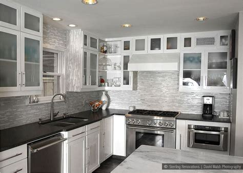 white kitchen cabinets with dark countertops black countertop brown backsplash white cabinet black
