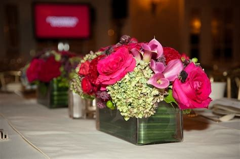 centerpiece rectangular vase overflowing with a lush arrangement in shades of raspberry