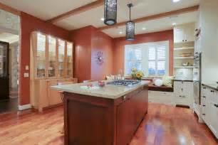 Terra cotta colored walls provide contrast to the painted cabinets and