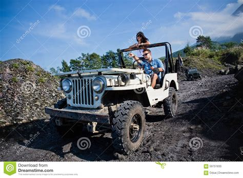 jeep couple mixed race couple riding a jeep off road stock photo