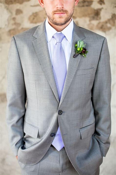 light grey tie groom is dressed in a light gray suit with a light blue