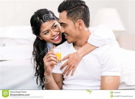 men in bed with other men asian couple embracing each other in bed stock photo