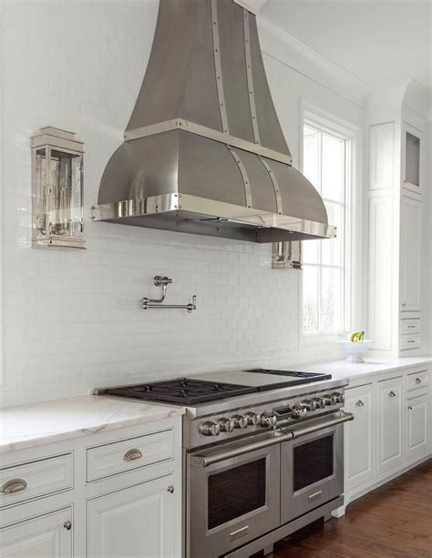 small white kitchen with steel hood kitchen hood between glass cabinets design ideas