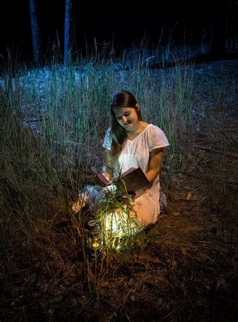 Young Woman Sitting At Night Forest Stock Photo