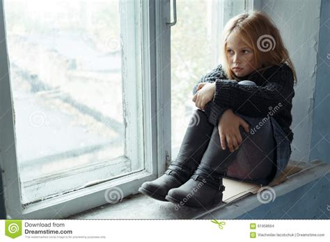 swing life stiles depressed poot girl standing near window stock photo