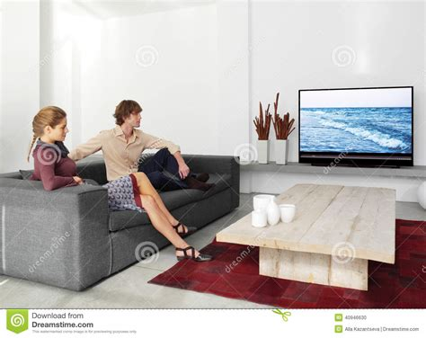 young couple room couple sitting on the sofa watching tv ll stock photo