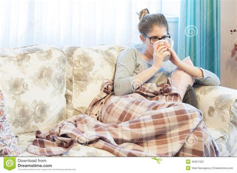 girl on the couch sick young woman sitting on the couch and drinking tea