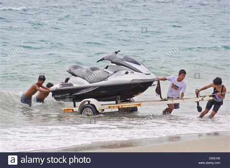 jet ski on boat trailer group of people pulling a jet ski out of the ocean on a