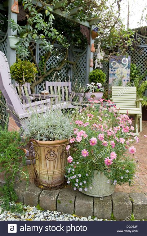 Patio in garden with late summer flowers in containers