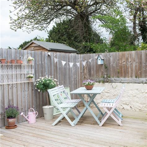 outdoor space with decking and pastel painted table and