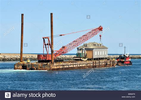 tugboat house tugboat pulling a house and crane on a barge stock photo