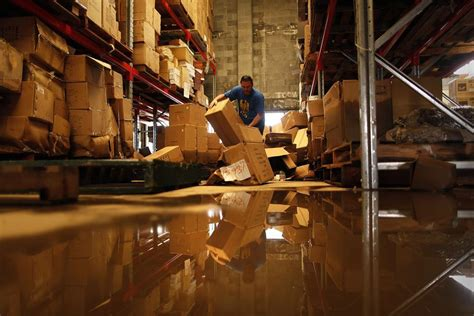 a man sorts through damaged merchandise in a flood hit