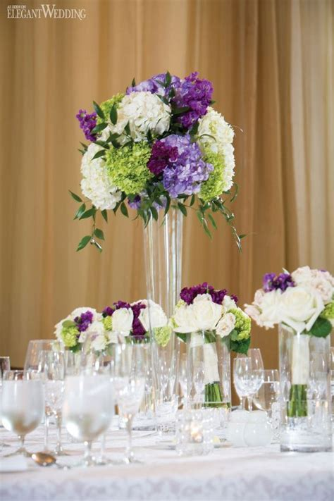 Purple and green floral centrepieces, wedding table