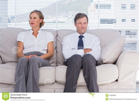 people on the couch two bored business people sitting on couch royalty free