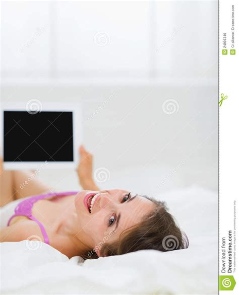 laying in bed smiling girl laying in bed and using tablet pc stock photo