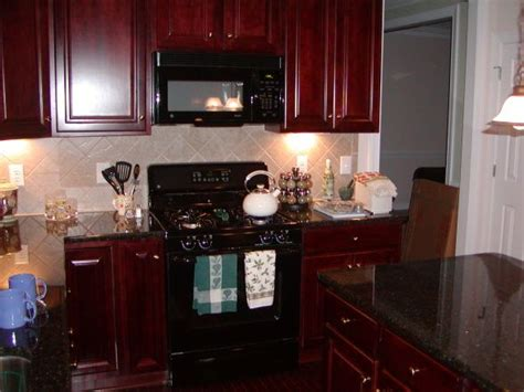 cherry kitchen cabinets with black granite my