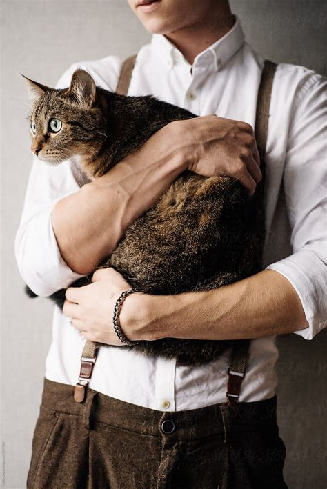 young man  holding  cat  laika  stocksy united