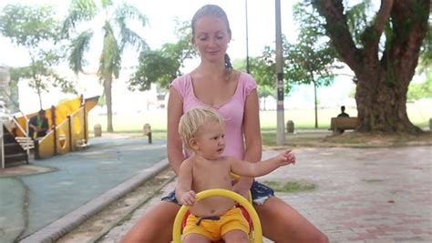 swinging for first time baby swings for the first time with mother on a swing in the park stock footage video 8399518