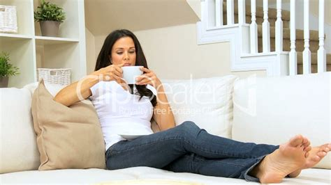 Average Couch Length brunette girl on home couch drinking coffee royalty free