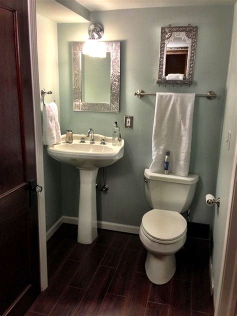 chosing powder room finishes just toilet and pedestal sink wood tile floors sleek and