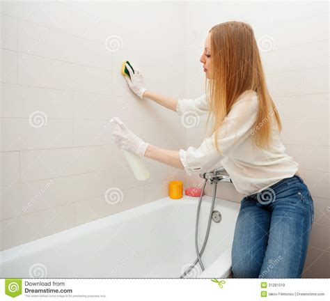 woman bathroom long haired woman cleaning tile with sponge in bathroom