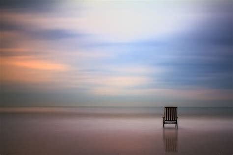 empty couch empty chair on the beach sunset empty wooden chair