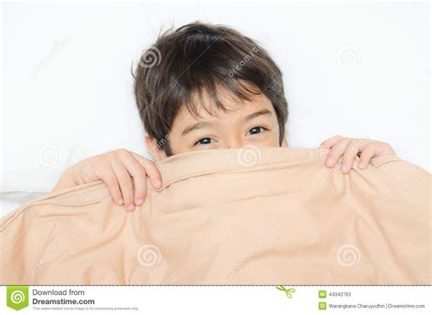 lay on the bed little boy lay on bed with blanket cover half face stock