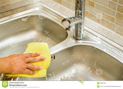 clean sink and faucet using yellow sponge stock