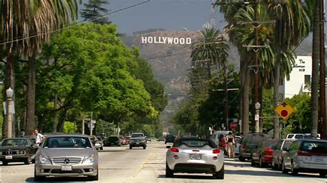 hollywood sign from street tilt up silver car driving along street with hollywood