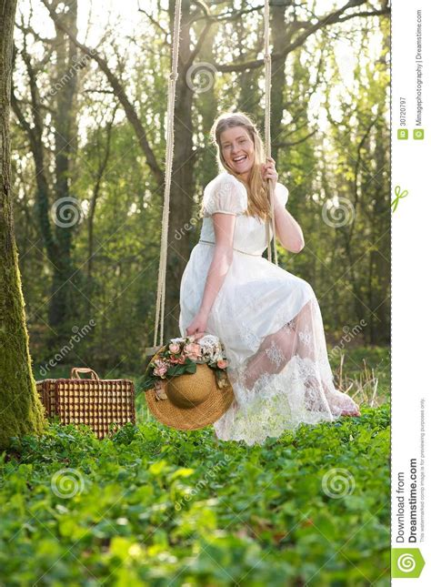 sitting on a swing happy young woman sitting on a swing outdors royalty free