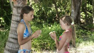 very young little girls smoking young girls under the coconut trees clean peel a banana