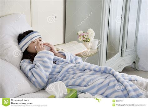 cold bed young woman lying on bed with common cold royalty free