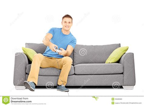 the man on the couch young smiling man seated on a sofa playing video games