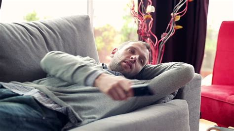 man on couch changing channels with a tv remote control stock footage