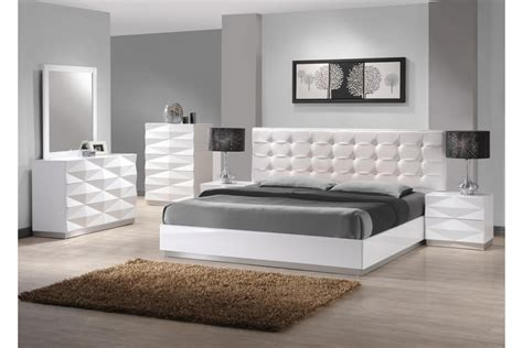 dark grey wooden bed with white leather headboard next to white wooden low profile king size bed with silver