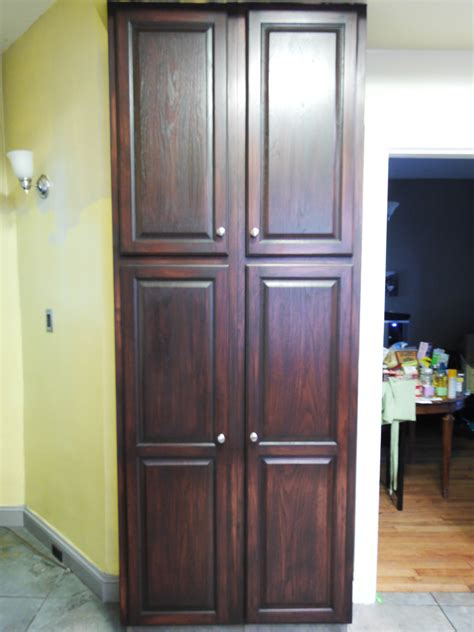free standing corner pantry cabinet on brown laminate wood
